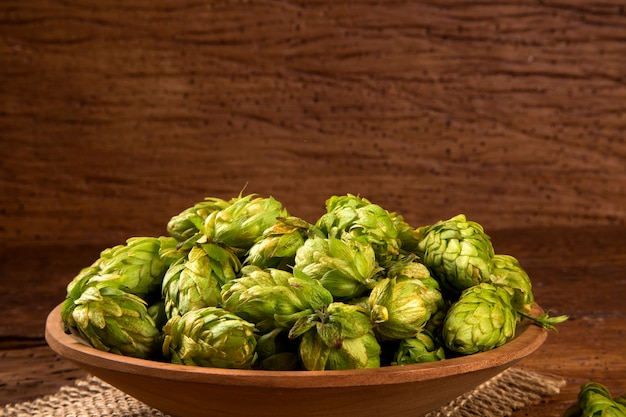 Beer brewing ingredients hop cones in wooden bowl and wheat ears on wooden background. beer brewery concept.