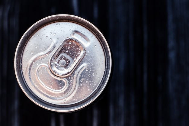 Beer can with condensation on black background. aluminium can of drink with water drops, refrigerated cola can, top view. text space.