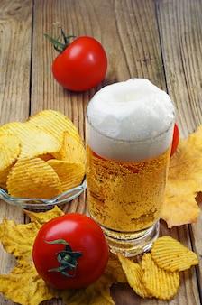 木製のテーブルにビール、チップス、トマト