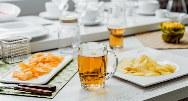 Beer and chips on the large white table