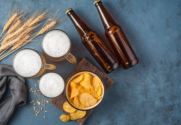 Beer chips and wheat spikelets on a dark blue background top view