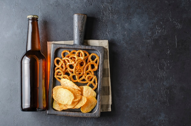 Beer in dark glass bottles and salty snacks. dark concrete background. top view. free space for text.