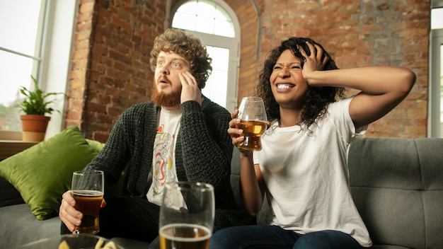Beer. excited couple, friends watching sport match, championship at home. multiethnic friends, fans cheering for favourite national basketball, tennis, soccer, hockey team. concept of emotions.