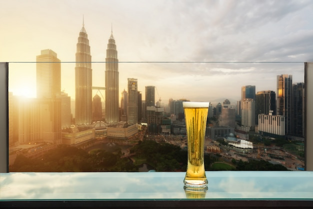 Beer and foam beer on table in rooftop bar with kuala lumpur, malaysia.