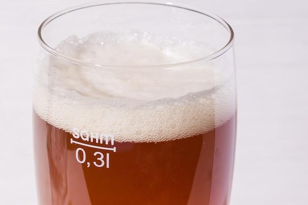 Пивная пена в стекле. домашнее крафтовое пиво из светлого солода на белом фоне. эль или лагер из солода пилснер