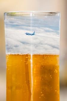햇빛에 유리 벽에 맥주 거품. 맥주 한 잔에 담긴 하늘과 비행기. 개념 - 우리는 술을 마시기 위해 휴가를 간다