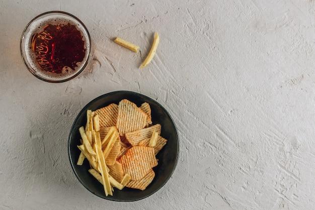Пивной стакан и картофельные чипсы в черной миске на бетонном фоне