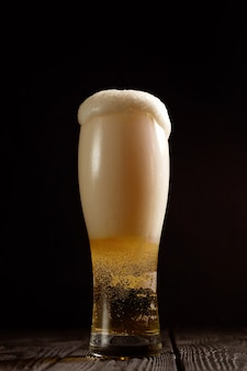 Beer in glass on black background, foam pours out of the glass