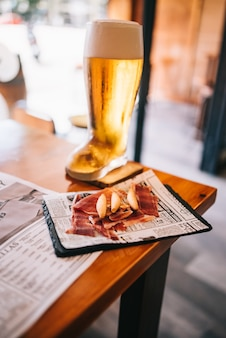 木製のテーブルの上においしいスペインのイベリコハムスナックとビールグラスブーツ