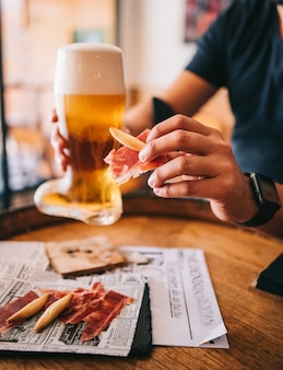 Beer glass boot with delicious spanish iberian ham snacks on a wooden barrel