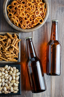 Beer in glass bottles and salty snacks for beer in wooden dishes