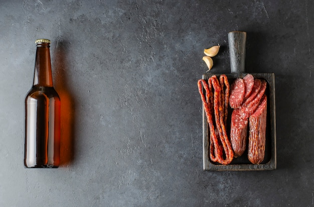Beer in glass bottles and sausage. dark concrete background. copy space.