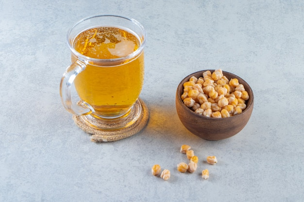 Beer glass and bowl of chickpea , on the marble surface.
