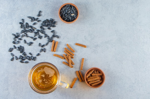 Bicchiere da birra e ciotola di crostini di ceci, semi, sullo sfondo di marmo.