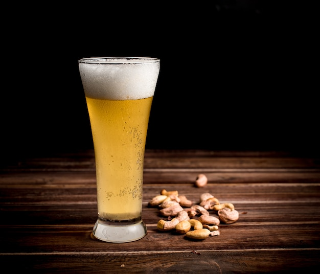 Beer glass and cashew nut on wood table,dark background