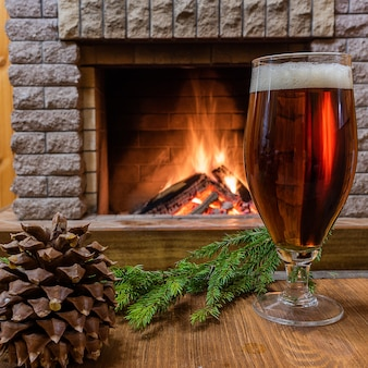 ビールグラス、コーン、居心地の良い暖炉に対してクリスマスツリーブランチ。 Premium写真