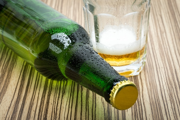 Beer in the glass and covers on wooden table