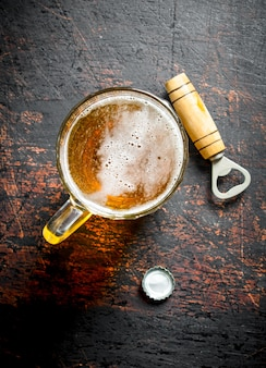 Beer in a glass cup and opener. on dark rustic background