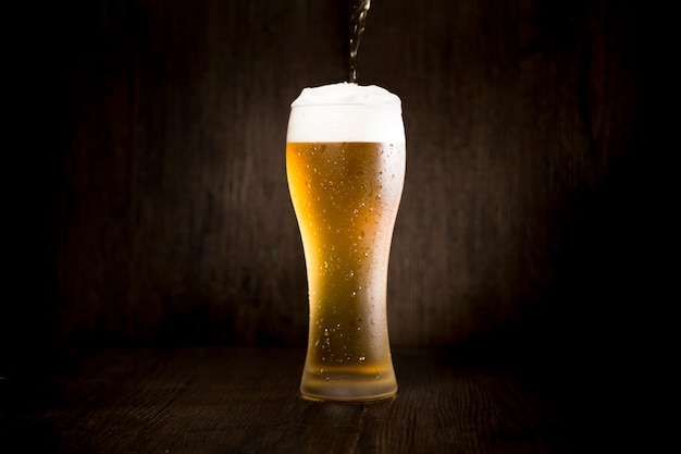 Beer glass in front of black background