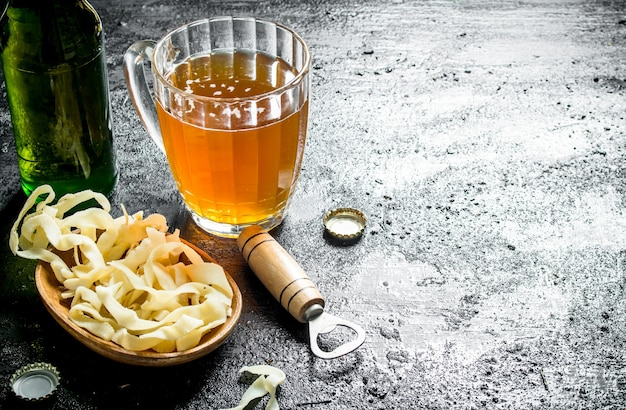 Beer in a glass mug and snacks in the bowl. on black rustic background