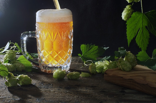 Beer in a glass mug with foam, the process of pouring on a black background.