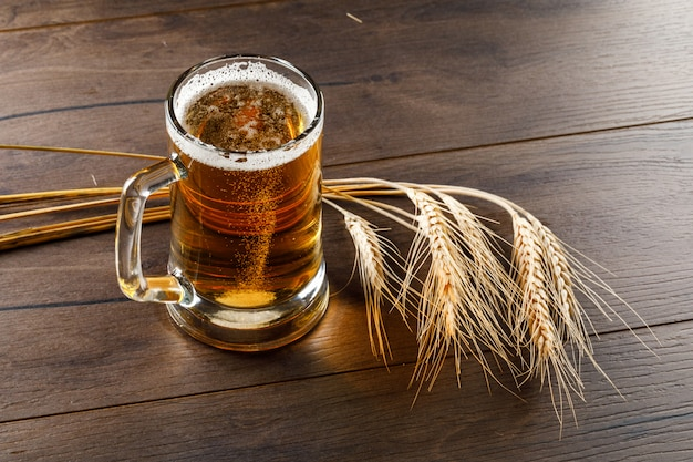 Beer in a glass mug with wheat ears high angle view on a wooden table