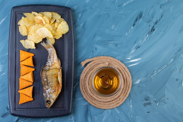 Пивной бокал на подставке рядом с чипсами и сушеной рыбой на подносе на синем фоне.