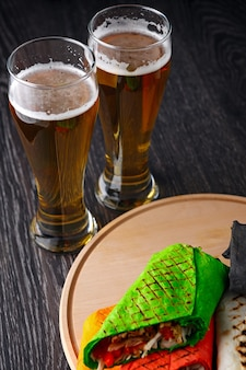 Beer in a glass and shawarma in pita bread is cut and lies on a wooden surface