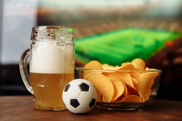 テレビの前にビアグラス、サッカーボール、チップス。サッカーファンのコンセプト。