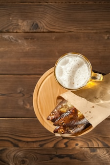 Beer glass with beer and hot smoked fish close-up. beer mug with beer and fish on a dark background and copy space.