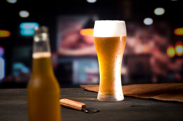 Beer glass with blurred bottle