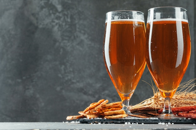 Beer glass with bretzel and dried sausages snacks close up
