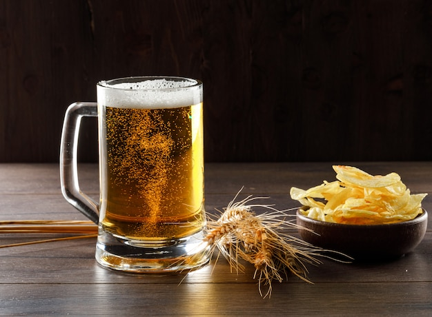 Beer in a glass with wheat ears, chips side view on a wooden table