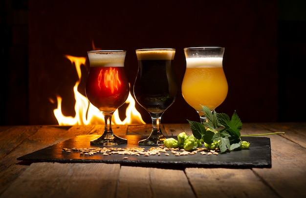 Пивные бокалы, ветка хмеля, зерна пшеницы на деревенском деревянном столе против огня