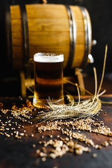 Beer glasses and wheat spice on an old rustic  wood table on black background