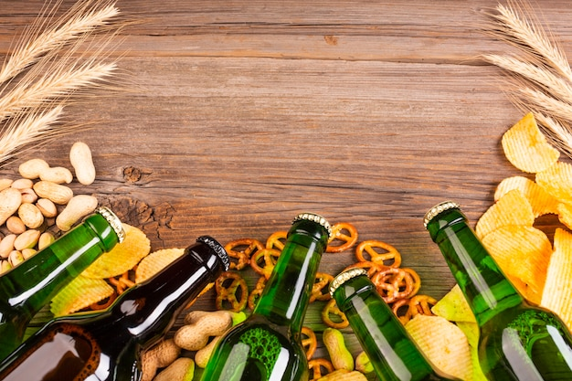 Beer green bottles frame with pretzels