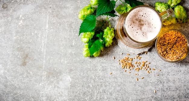 Пиво, зеленый хмель и солод на каменной поверхности. вид сверху