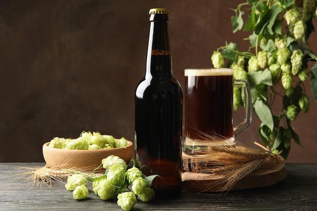 Пиво, хмель и пшеница на деревянном столе против коричневого стола
