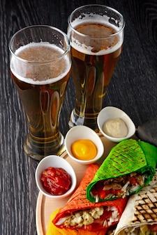 Пиво в стакане и шаурма в лаваше нарезается и лежит на деревянной поверхности
