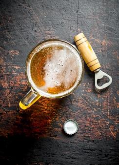 ガラスのカップとオープナーのビール。暗い素朴な背景に