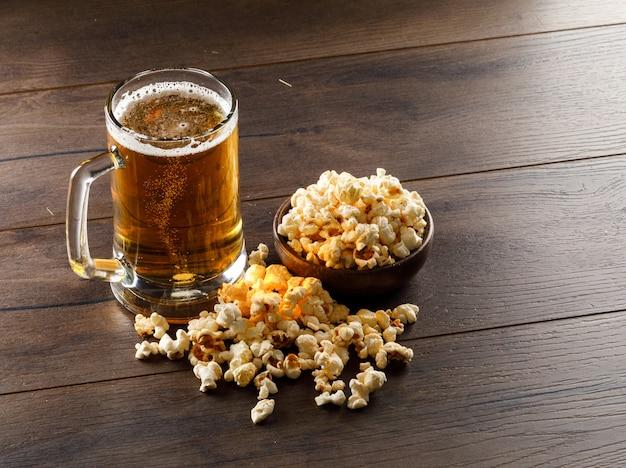 Пиво в стеклянной кружке с большим углом попкорна на деревянном столе