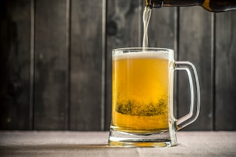 Beer in a glass pours out of a bottle.