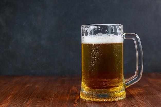暗い背景がある木製のテーブルの水滴とマグカップでビール