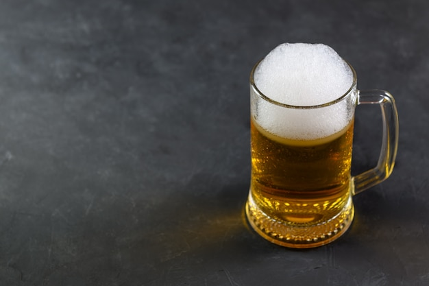 Пиво в кружке с каплями воды на деревянный стол на темном фоне