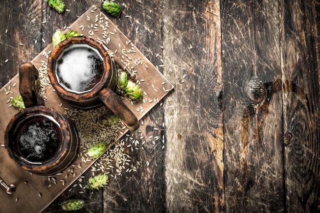 나무 배경에 녹색 홉과 나무 머그잔에 맥주