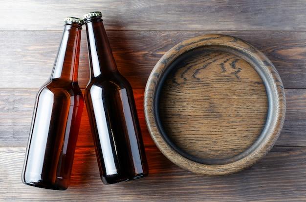 Пиво в стеклянных бутылках и деревянной тарелке для закусок. коричневый деревянный фон.