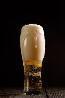 黒地にグラスのビール、泡がグラスから注がれる