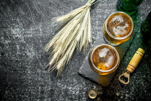 素朴なテーブルの上のグラスと小穂のビール