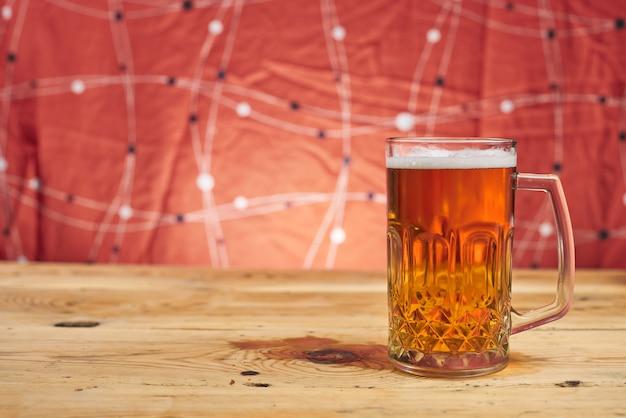 木製のテーブルのマグカップの中のビール