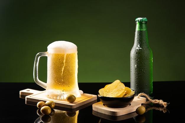 Пивная кружка и пиво с закусками на зеленом и темном фоне.